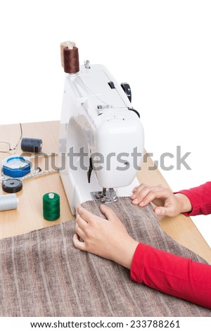 Industrial sewing machine and hand seamstress. Close-up. - stock photo