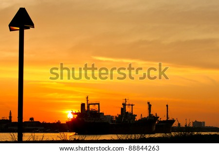 industrial ship and factory silhouetted at sunset with river