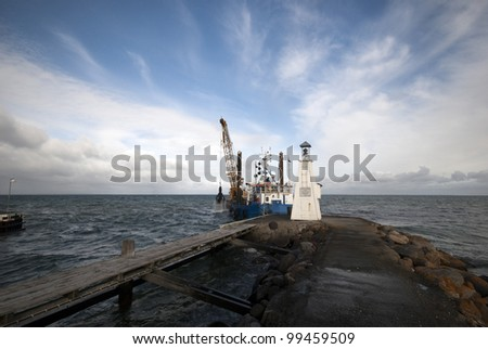 Industrial ship digs sand making harbor entrance deeper for bigger ships to be able to dock in Bogense port, Denmark