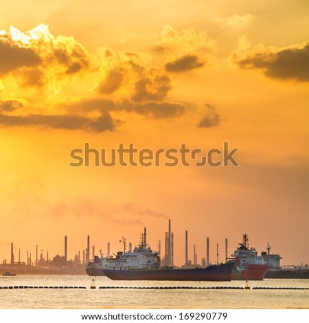 Industrial ships in front of refinery and heavy industry in the sunset. Environment pollution issue. - stock photo