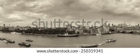 Industrial ships on river Thames, London skyline in background. - stock photo