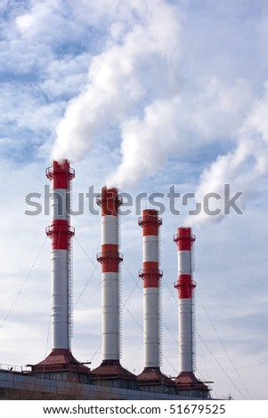 Industrial site with smoking chimneys, steam against blue sky with clouds. - stock photo