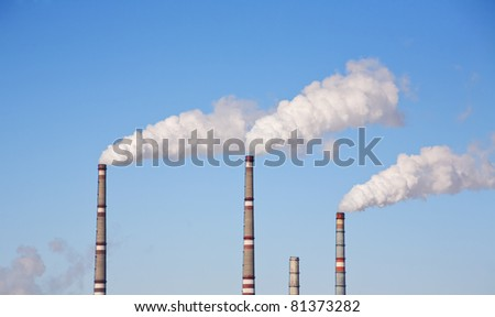 industrial smoke comes out of a chimney  against  the  blue sky - stock photo