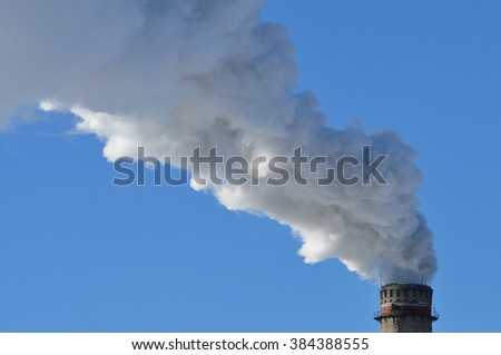 industrial smoke from chimney on blue sky day - stock photo