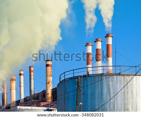 Industrial smoking chimneys against the blue sky - stock photo