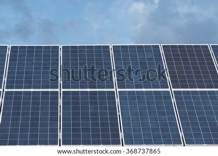 Industrial Solar Panels against Deep Blue Sky