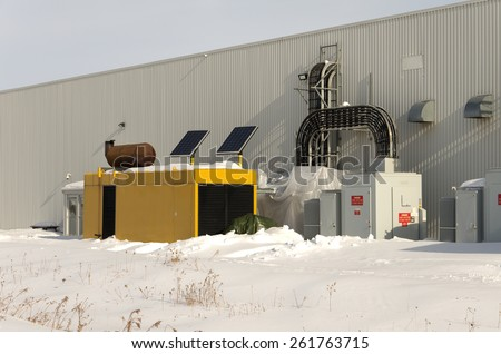 Industrial standby generator and electrical service with solar panels in winter. - stock photo