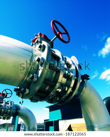 Industrial Steel pipelines and valves  against sky - stock photo