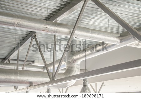 Industrial steel ventilation pipes inside of building. - stock photo