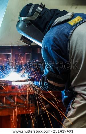 Industrial steel welder in factory - stock photo
