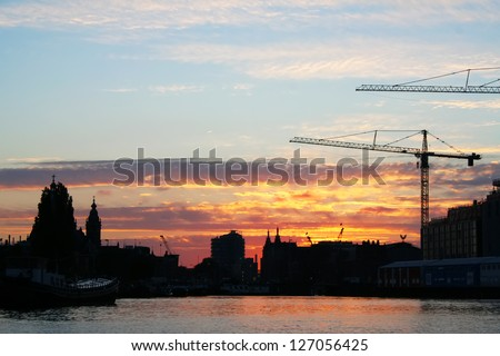 Industrial sunset on the river with crane - stock photo