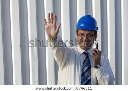 Industrial surveyor on location talking on his radio and signaling to stop - stock photo