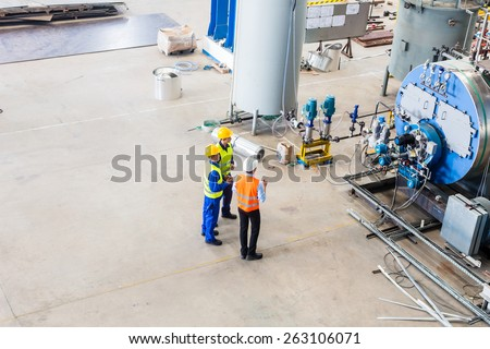 Industrial team of Worker and engineer discussing at machine in factory - stock photo