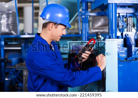 industrial technician examining control box with digital insulation tester - stock photo