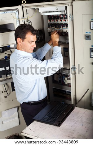 industrial technician repairing computerized machine with laptop computer - stock photo