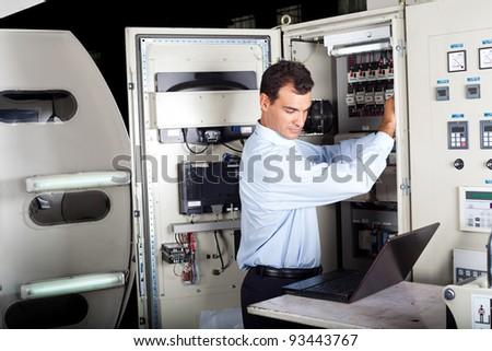 industrial technician repairing modern computerized machine in factory - stock photo