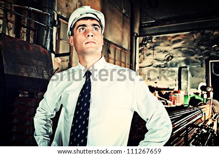 Industrial theme: businessman at a manufacturing area. - stock photo