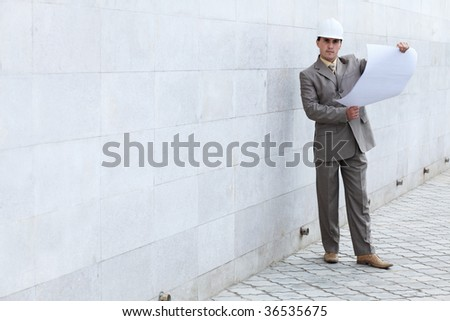 Industrial theme: constructor standing at a building site. - stock photo