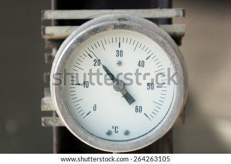 Industrial thermometer isolated on gray metallic background - stock photo
