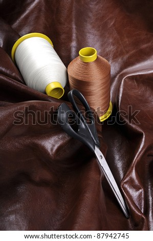 Industrial thread bobbins on a real leather background