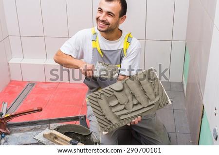 industrial tiler builder worker installing floor tile  - stock photo