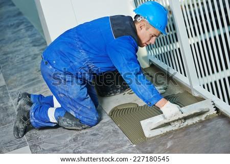 industrial tiler builder worker installing floor tile at repair renovation work - stock photo