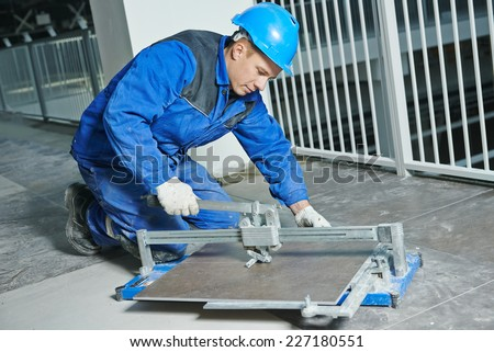 industrial tiler builder worker working with floor tile cutting equipment at repair renovation work - stock photo