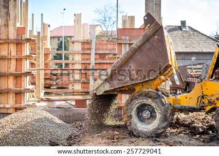 industrial truck loader excavating gravel and construction aggregates. Construction site with dumper truck and materials - stock photo
