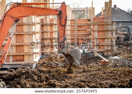 Industrial truck loader excavator moving earth and leveling a ground hole - stock photo