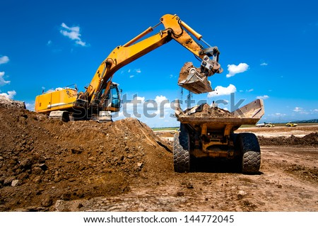 Industrial truck loader excavator moving earth and unloading into a dumper truck - stock photo
