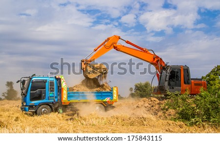 Industrial truck loader excavator moving earth and uploading into a truck. - stock photo