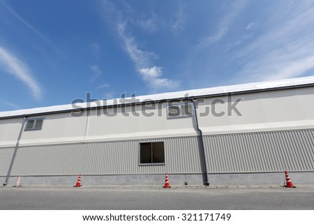 industrial warehouse against a blue sky - stock photo
