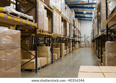 industrial warehouse interior with shelves and pallets with cartons - stock photo