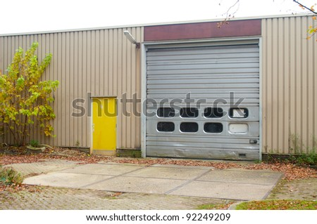 industrial warehouse with damaged roller door - stock photo