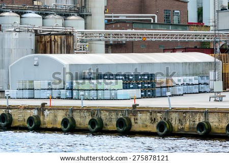 Industrial warehouse with lots of pallets and barrels outside. Industry in background, water in front. Harbor area. - stock photo