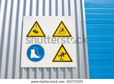 industrial warning signs on a warehouse with a blue roller door