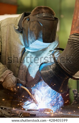 Industrial welder worker welding steel at factory workshop with welding fume and dust extractor and flying sparks - stock photo