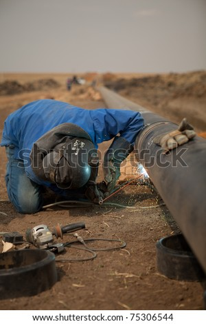 Industrial welder working on oil and gas pipeline - stock photo