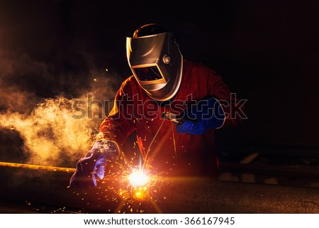Industrial Worker at the factory welding closeup - stock photo