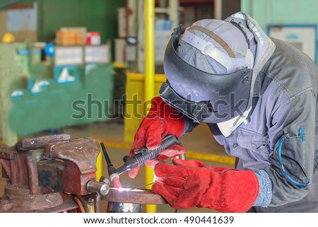 Industrial Worker at the factory welding pipe by Tig