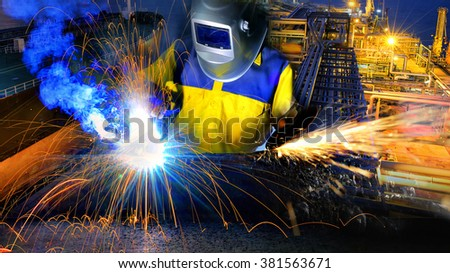 Industrial Worker at the refinery welding and electric wheel grinding close up. - stock photo