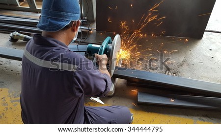 Industrial worker cutting a metal with many sharp sparks - stock photo