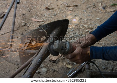 Industrial worker cutting and welding metal with many sharp sparks. - stock photo