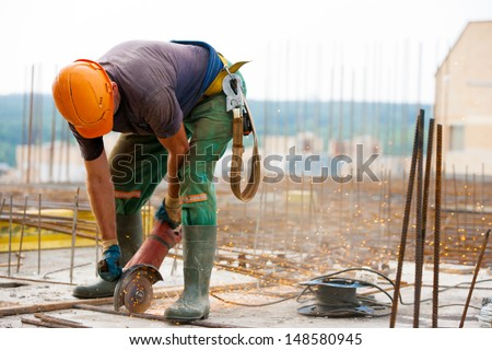 Industrial worker Cutting metal rebar at Construction site with an electric hand Grinder machine during tying steel bars for concrete reinforcement - stock photo