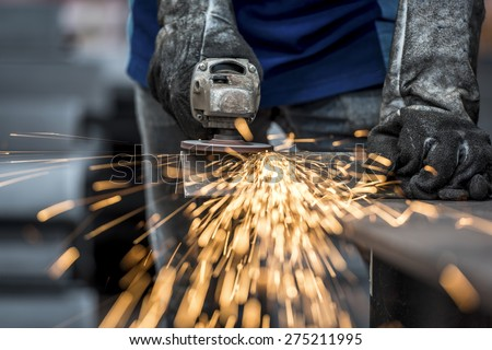 Industrial worker cutting metal with many sharp sparks - stock photo
