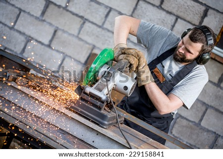 Industrial worker cutting metal with many sharp sparks working on compound mitre saw with circular blade  - stock photo