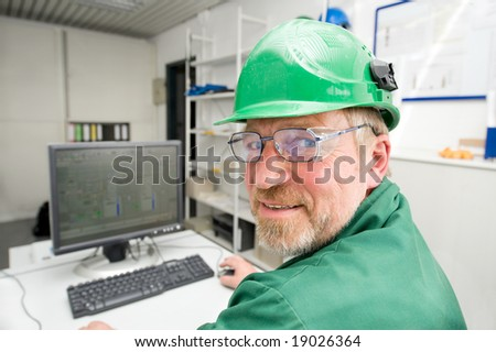 Industrial worker in his office in front of a pc - stock photo