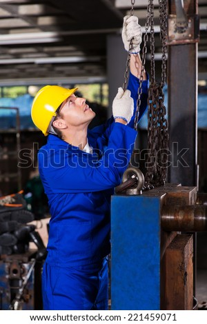 industrial worker in uniform pulling chains - stock photo