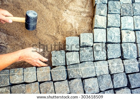 industrial worker installing pavement rocks, cobblestone blocks on road pavement - stock photo