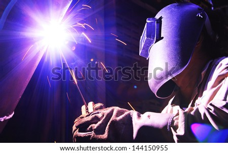 Industrial worker make a spark welding, working place background. - stock photo